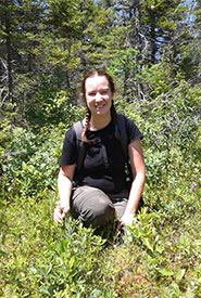 Joanna Hudgins, NCC intern, happy to be in a bog in the Chignecto Isthmus, NB, with a white-fringed orchis. (Photo by Claire Elliott).