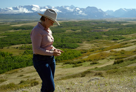 Kathy Flundra, checks on her grass at the height of her ranch, a part of the Park Front Project. The mountains of Waterton complete the vista. (Photo by Ann Tipper and Zach Melnick)