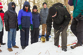 Scouts pouring hot maple syrup on snow to make maple taffy (Photo by Andrea Burbidge Photography)