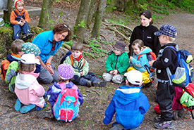 A teacher conducts a lesson in the forest (Photo by the Nature Office for the International Day of Forest Kindergarten)
