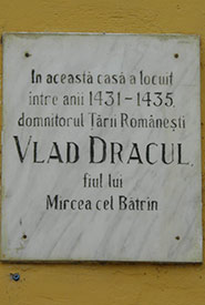 """Romanian sign on building in Sighişoara, Transylvania that reads, """"In this house between 1431-1435 lived the rule of the Romania country Vlad Dracul. Son of Mircea cel Bâtrin."""" (Photo by Katie Bell)"""