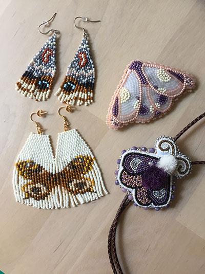 Four moth beadwork pieces (From top left clockwise:  xʷəlməxʷ beadwork @xwelmexwbeadwork, Reags Beads @reagsbeads (pink moth pin), Story Bead Creations @manidoominens_adizookaan (moth bolo), Diving Loon Co. (@divingloonbeads))