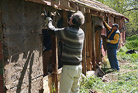 Volunteers at the Bears in Mind event help bring down an old structure on NCC property (Photo by NCC)