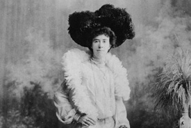 Woman, wearing a large feathered hat and boa, posing for a portrait (Photo by John Oxley Library, Public Domain)