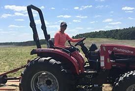 NCC intern Breanna Silverside on a tractor that pulls the industrial mower. (Photo by NCC)