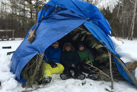 Build a shelter by gathering materials for insulation. (Photo by Scouts Canada)