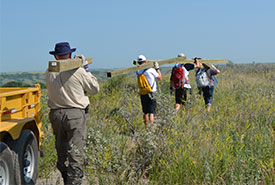 Volunteers carry sign posts to designated spot at Fairy Hill property for interpretive sign installation. (Photo by NCC)