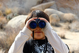 Child with binoculars (Public Domain)