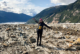 Justine standing on the rocky side of Meade Glacier (Photo courtesy of Justine Coutu)