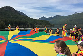 A parachute demonstration helps Grade 4/5 students learn what a watershed is, in the upper Nanaimo River watershed at Jump Lake dam with the RDN, Mosaic Forest Management and the City of Nanaimo. (Photo by Regional District of Nanaimo)