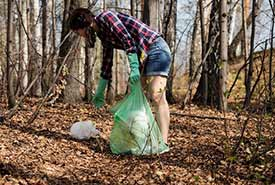 Woman picking up trash in a forest (Photo by Anastasia Gepp, Pixabay)