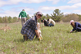 Victoria Shore planting native species while working as an intern at NCC (Photo by NCC)