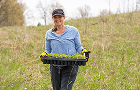 Volunteer with tray of seedlings at Goulding West property, Ontario (Photo by Neil Ever Osborne)