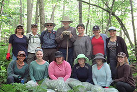 Conservation Volunteers pose with their bags of creeping Jenny at the end of day tackling this invasive species (Photo by Cheryl Spotswood)