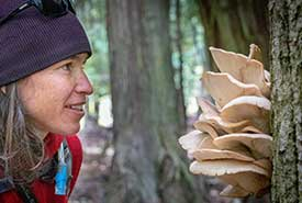 A participant inspects a mushroom (Photo by Pat Morrow)