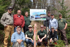 Happy volunteers, including members of the local ATV club,  pose after a hard day's work of driving posts and installing signage to protect snapping turtle habitat at Silver River, NS. (Photo by NCC)