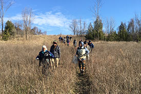 Volunteers hike to the tree planting site at NCC's Ashton Potter property in the Lower Maitland River Valley, ON (Photo by NCC)