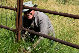 A conservation volunteer cleans the bison handling facility at Old Man on His Back. (Photo by Gail Chin)