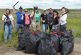 Conservation Volunteers with bags of invasive common burdock. (Photo by NCC)