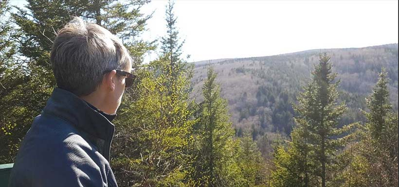 Denise Roy looking out at the forests of Riverside Albert, NB (Photo by NCC)