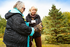 Joanne Laskin and Kim Blomme, gathering for nature, Bunchberry meadows, AB (Photo by Kyle Marquardt)