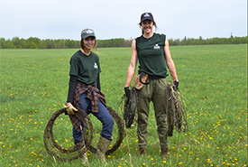 Emma and Nicole are carrying barbed wire to clear the way for wildlife. (Photo by NCC)