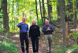 Paul Smith (right) takes a walk through the forest he transferred to NCC, with Karen Clarke-Whistler, chief environment officer of TD Bank Group, and John Lounds, NCC president and CEO (Photo by Simon Wilson)Paul