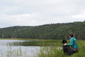 NCC Program Director Lanna Campbell and Polly look out over the Salmonier River (Photo by Trevor Nickerson)