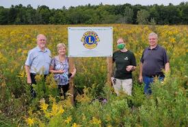 Paul De Cloet, Josiane De Cloet, Liv Monck-Whipp, Ron Keba stand in front of sign to commemorate Lion's Club centennial tree planting project. Photo by NCC.