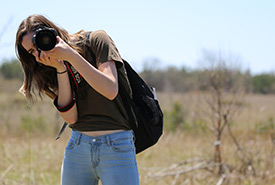 Chelsea Marcantonio, 2018 conservation intern photographing a prescribed burn on the Rice Lake Plains, ON (Photo by Cameron Curran)
