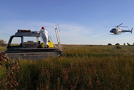 Marsh master and helicopter, Long Point, ON (Photo by Giles Restoration Services Inc.)