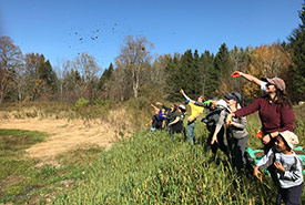Seeding the wetland with mudballs, Creemore Nature Reserve, ON (Photo by NCC)