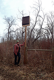 Sarah beside a recently installed bat house at Fairy Hill, SK (Photo by Lorena Squires)